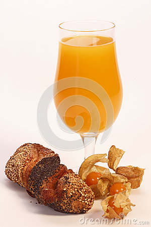 Glass of fruit juice with a physalis and bun