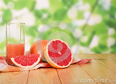 Glass of grapefruit juice and sliced ​​on table in yard