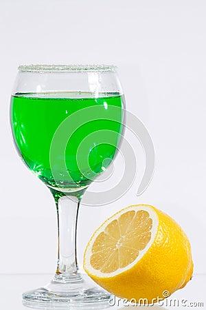 The glass of green liquor and lemon
