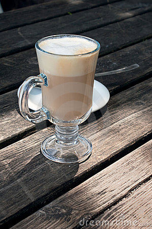 A glass of hot latte macchiato on a wooden table