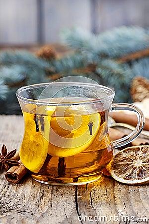 Glass of hot steaming tea among christmas decorations