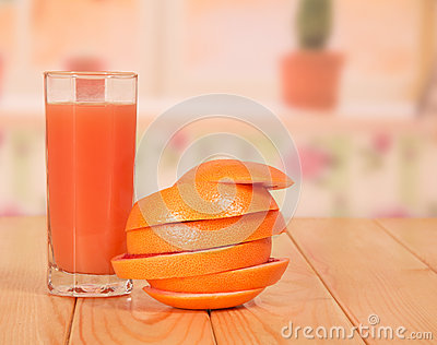 Glass of juice, grapefruit sliced rings and stacked