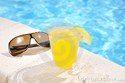Glass of juice and sun glasses