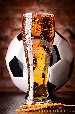 Glass of lager on table with soccer ball