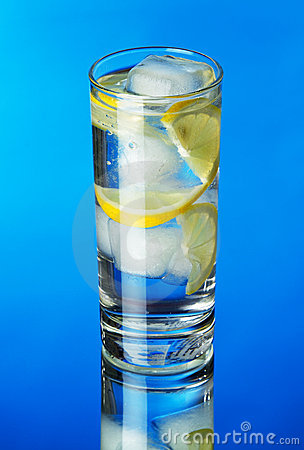 Glass of lemon ice water on blue background