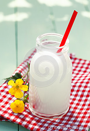 Glass milk bottle on checkered tablecloth