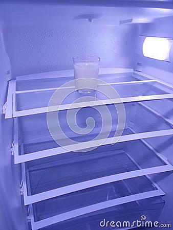 Glass of milk in empty refrigerator