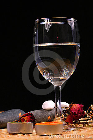 Glass, natural bebbles and dried flowers on the rattan background