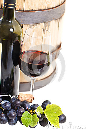 Glass of a red wine, bottle, barrel and grapes