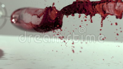 Glass of red wine falling and spilling. In slow motion stock footage