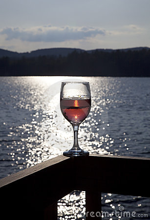 Glass of red wine at lake
