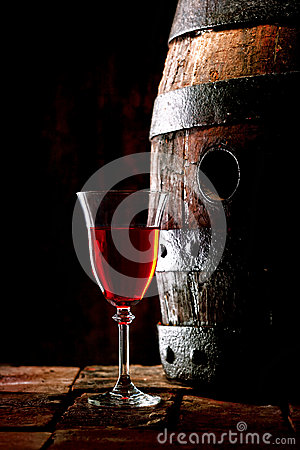A glass of red wine next to an oak cask