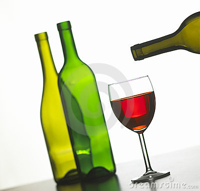 Glass of red wine with two green wine bottles