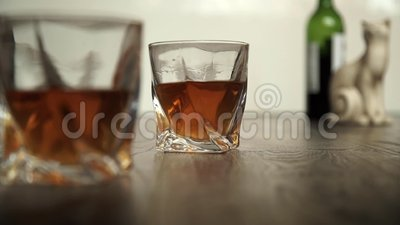Glass of scotch whiskey and ice in hand stock video