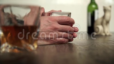 Glass of scotch whiskey and ice in hand stock footage