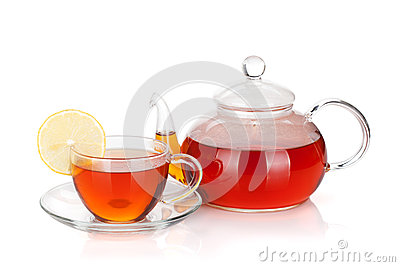 Glass teapot and cup of black tea with lemon slice
