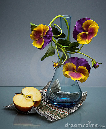 Glass vase with pansy and apple on black
