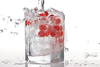 Glass of water, ice and red cranberry with splash