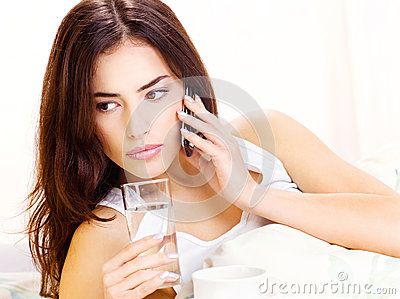 Glass of water and phone in bed