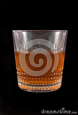 Glass of whiskey on dark background