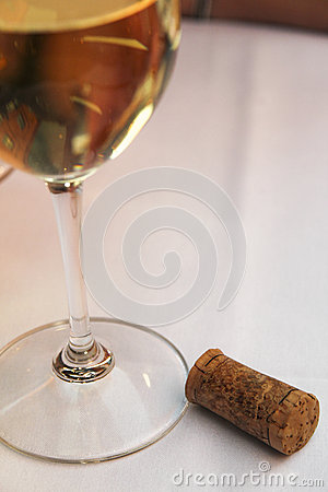 Glass of White Wine with Cork on White Linen Table