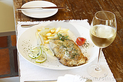 glass of white wine with fish and chips royalty free stock