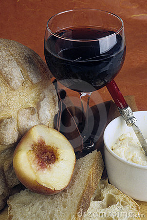 Glass of wine with bread, peach and cheese