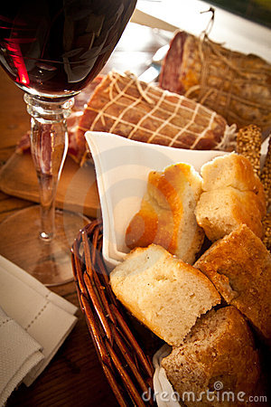 A glass of wine, bread and salami close-up