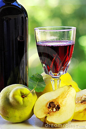 Glass of wine and quince fruits.