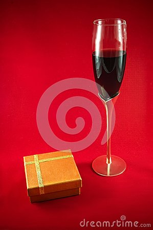 Glass wineglass, red wine and gift box on red back