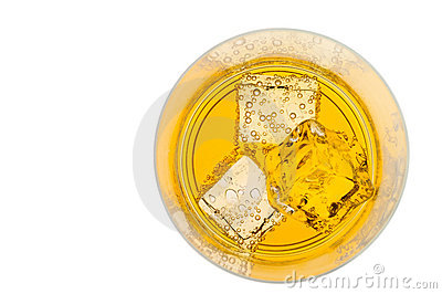 Glass of yellow drink with ice