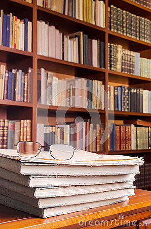 Glasses and books on library table