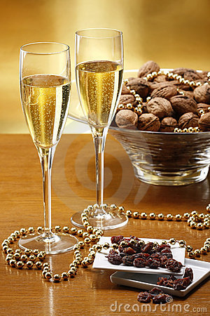 Glasses of champagne with gold background walnuts