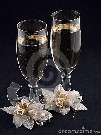 Glasses with champagne and weddings buttonholes