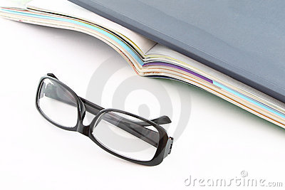 Glasses in front of opened magazines