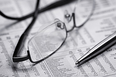 Glasses on a newspaper with a pen