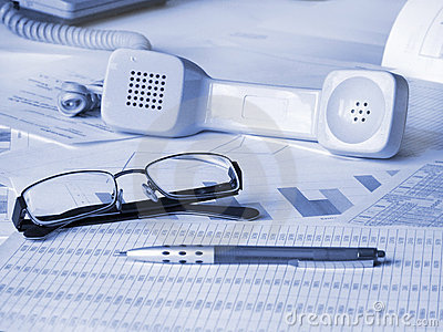 Glasses, pen and phone on financial documents