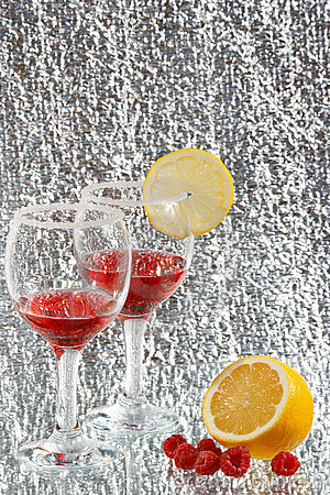 The glasses of red liquor, lemon and raspberries