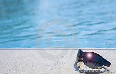 Glasses on a  swimming-pool edge