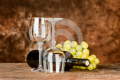 Glasses with wine bottle and grapes