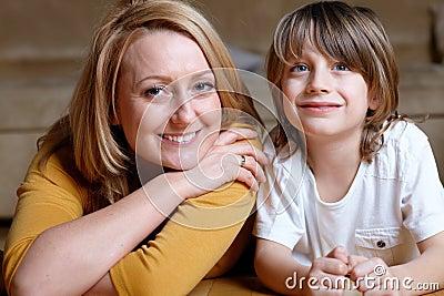 Glückliche junge Mamma, die auf Fußboden mit ihrem Sohn liegt