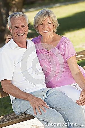 Glückliche ältere Paare, die draußen im Sonnenschein lächeln