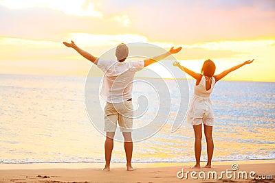 Glückliche zujubelnde Paare, die Sonnenuntergang am Strand genießen