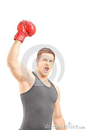 Glücklicher männlicher Boxer, der rote Boxhandschuhe trägt und Triumph gestikuliert
