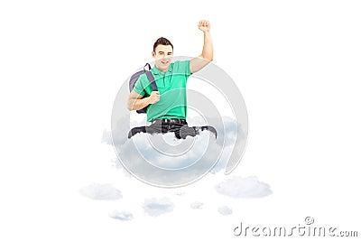 Glücklicher männlicher Student, der auf einer Wolke mit dem angehobenen Handgestikulieren sitzt