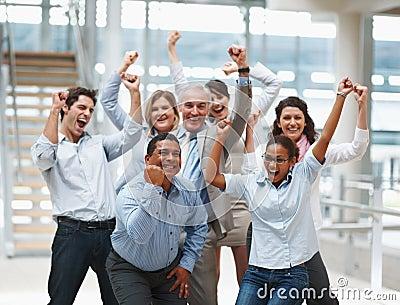 Glückliches multi ethnisches Team mit den Händen angehoben
