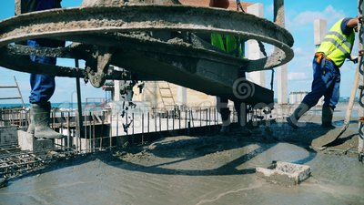 Gli ingegneri coprono il pavimento con il cemento in un cantiere archivi video