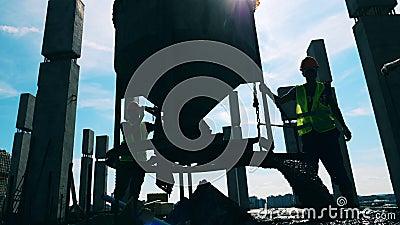 Gli ingegneri lavorano con una macchina, versando cemento su un pavimento video d archivio