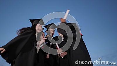 Gli studenti che si laureano felicemente si stanno abbracciando e stanno facendo cinque anni dopo la cerimonia della laurea stock footage