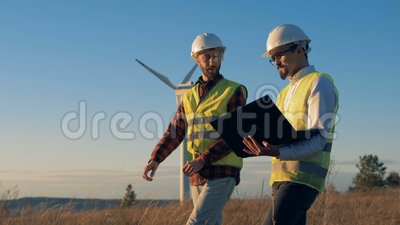Gli uomini discutono un progetto mentre controllano i generatori eolici nel campo Concetto ambientale di energia archivi video